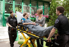 Emergency Care. Senior woman with care giver being transported on stretcher by paramedics