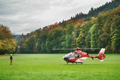 Emergency doctor helicopter German red Cross. A rescue helicopter of the German Red Cross grounded in the middle of a field. A man wearing a helmet standing in Stock Photos