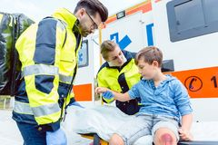 Emergency doctors caring for accident victim boy Stock Images