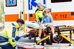 Emergency doctors caring for accident victim boy. Sitting on stretcher royalty free stock photography