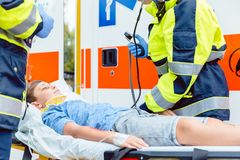 Emergency doctors putting injured boy in ambulance. Car Royalty Free Stock Photos