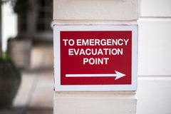 Emergency Evacuation Point. Sign with arrow pointing to an emergency evacuation point Stock Photos