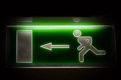 Emergency exit. Fluorescent emergency exit sign in dark wall Stock Photo