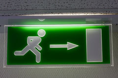Emergency exit. Fluorescent emergency exit sign in dark wall Royalty Free Stock Photography