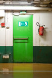 Emergency Exit Door. Green emergency exit door. French sign above the door and red fire extinguisher to the right Royalty Free Stock Image