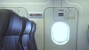 Emergency exit door and empty passenger seats inside commercial airplane. Interior modern passenger aircraft, passengers. Chairs and emergency door exit stock video