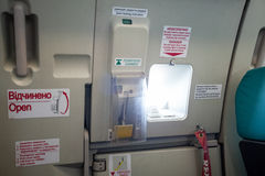 Emergency exit door with porthole in airplane Stock Photo