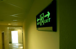 Emergency exit sign in a building glowing green  Royalty Free Stock Photo