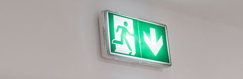 Emergency exit sign in a building glowing green. Emergency exit sign on a wall Stock Images