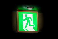 Emergency exit sign glowing in the dark Stock Image