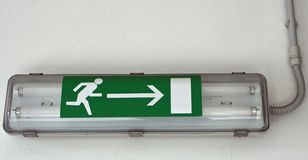 Emergency exit sign installed. Lamp with the emergency exit sign installed within a European factory royalty free stock images