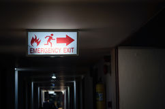 Emergency exit sign light showing way to escape in dark path way at night. Time Stock Photos