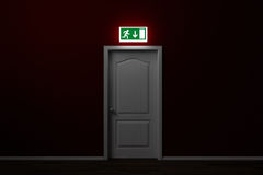 Emergency exit with sign over door. Emergency exit with glowing sign over door in a room Royalty Free Stock Image