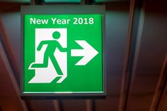 The board pointing way to New Year 2018. The emergency exit sign shows the direction of escape for happy New Year. The board pointing way to New Year 2018 Royalty Free Stock Photos