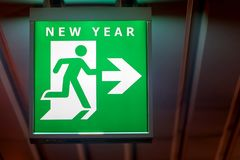The board pointing a way to New Year. The emergency exit sign shows the direction of escape for happy New Year. The board pointing a way to New Year Royalty Free Stock Image