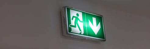 Emergency exit sign in a building glowing green. Emergency exit sign on a wall Stock Photos