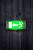 Emergency exit sign. On wooden plank wall Stock Image