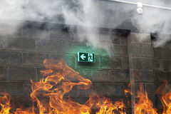 Emergency Fire Exit on the stone wall with fire and smoke stock photo