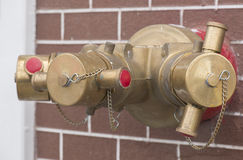 Emergency fire extinguisher water hydrant pipe on brick wall. Stock Images