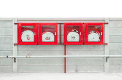 Emergency fire hose inside a glass fronted box mounted on a wall stock images