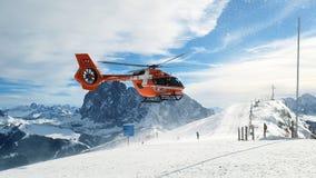 Emergency helicopter on ski slopes. Emergency helicopter hovering above ski slopes of Val Gardena near Santa Cristina, Dolomite Alps, Italy stock photography
