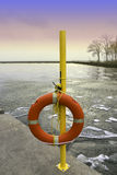 Emergency life preserver hanging on a yellow pole by an icy wint. Er lake at sunset Stock Image