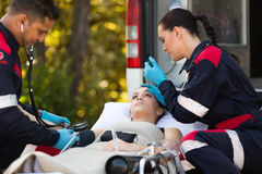 Emergency medical technicians patients. Team of emergency medical technicians checking patients vital signs stock images