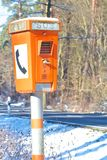 Emergency Phone 1. Orange emergency phone standing next to a dangerous and accident-prone winter road in Germany Royalty Free Stock Photos