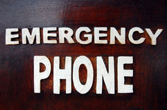 Emergency phone inscription. Vintage emergency phone inscription on wooden background Stock Photo