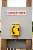 An emergency phone located on a wooden billboard.  Stock Images