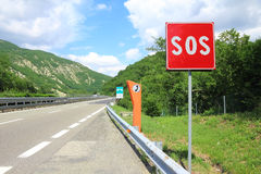 Emergency phone and sos sign on road. SOS sign and phone box on highway royalty free stock photography