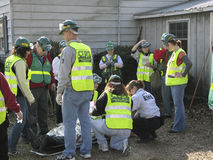 Emergency respond team helping injured person. This is horizontal image with sceene of emergency cituation. Several people  are wearing bright yellow safety vest Royalty Free Stock Photo