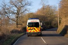 Emergency Service. Ambulance about to overtake a tractor, rural UK royalty free stock photography