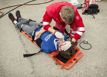 Emergency service worker makes the control of vital functions. Nitra, Slovakia - September 06, 2014: Simulation of the car accident. Emergency service worker Royalty Free Stock Photography