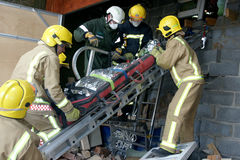 Emergency services at building collapse. Emergency services removing casualty at building collapse royalty free stock photography