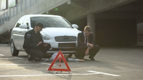 Emergency sign on road, policeman with male driver writing report, car accident. Stock footage stock video footage