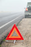 Emergency stop sign. The image of emergency stop sign under the frontground and part of blurred broken car under background. Focus is under the sign royalty free stock image