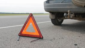 Emergency stop sign. The warning triangle is on a paved road behind the car SUV. On the highway passing cars stock video
