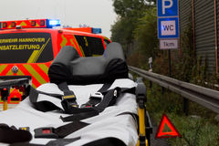 Emergency stretcher stands with a  german firefighting truck on freeway Royalty Free Stock Images