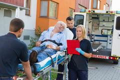 Emergency team assisting injured man on stretcher Royalty Free Stock Photography