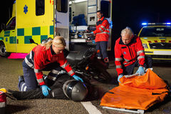 Emergency team assisting injured motorbike driver Stock Photos