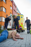 Emergency team assisting unconscious man on street Stock Photography