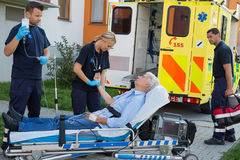 Emergency team examining patient on stretcher Stock Photo