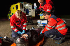 Emergency team helping injured motorbike driver Stock Photo