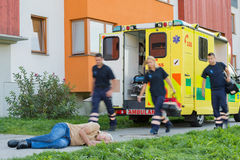 Emergency team running to unconscious man Stock Images