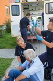 Emergency team treating injured patient on street Stock Photography