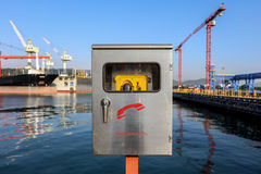 Emergency telephone box. Emergency telephone yellow color cover by stainless steel box with handle, background are quayside have tower crane and cargo vessel royalty free stock photos