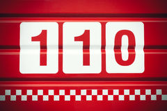 Emergency telephone number. 110 for fire written on fire truck back side royalty free stock images