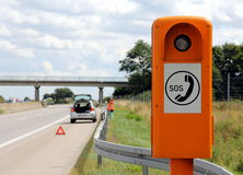 Emergency telephone at the roadside. Emergency telephone on a German highway (Autobahn) with car broken down in the background, hazard flashers turned on,  Stock Images
