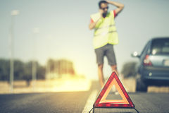 Emergency triangle with man and car in the background. Royalty Free Stock Image